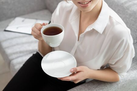 Young beautiful blonde girl with short hair in a white shirt and glasses is sitting on the sofa in bright in the office against the window. Holds a white cup and saucer. Drinking coffee or tea in a working break. Relaxation concept.