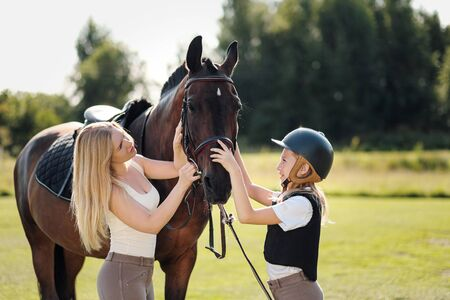 Madre e hija jinetes y jinetes en un campo verde abrazan a un caballo marrón. Mentor y alumno. Foto de archivo