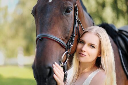 Young attractive blond woman hugs a brown horse. Face close up.