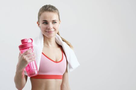Sporty blonde girl with a white towel around her neck, in red sportswear and with white wireless headphones on a light background. Red water bottle. Drinks liquid.