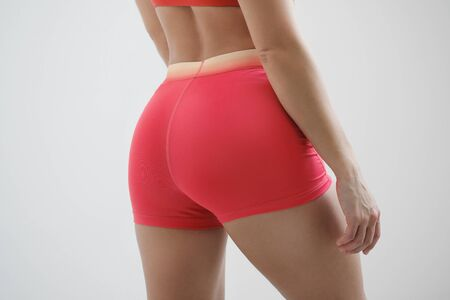 Booty girl in a red sportswear on a light background close-up.