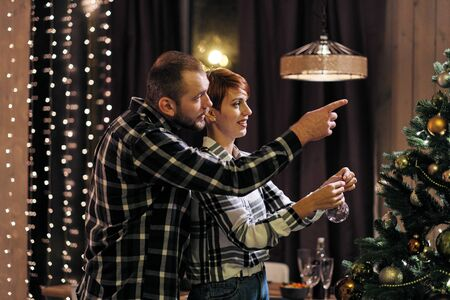 Young married couple at home in casual clothes, a man and a woman decorate the Christmas tree, get ready for the holiday.
