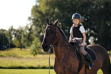Girl teenager jockey sits on a brown horse in nature. Dressage horses, rider training. Stock Photo