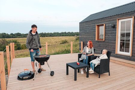 A young Caucasian family couple with a baby daughter sits on the terrace in chairs and drinks hot drinks. Against the background of a small modern rustic wooden house. Father is cooking barbecue. Summer evening in the village.