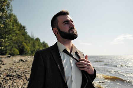 Young attractive male businessman in a brown suit with a briefcase stands on the seashore. Unfastens shirt, loosens tie and raises hands to sea. Relaxation and outdoor recreation. Banco de Imagens