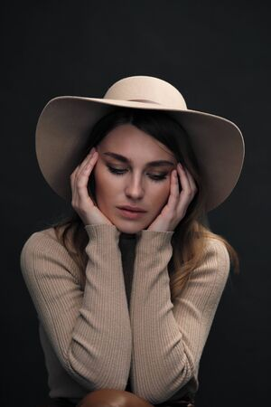 A young   woman with a beautiful face and clear natural skin poses in the studio against a black background. Beige slinky sweater and hat with fields. Beautiful folded hands and an attractive look.