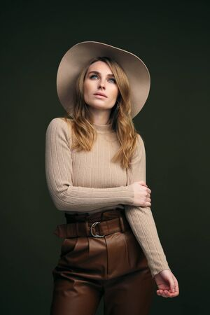 A young attractive blonde woman in a beige sweater, fedora hat and brown leather trousers poses on a dark green olive background. Studio portrait of a beautiful girls face.