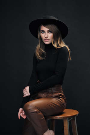 Portrait of young beautiful blond woman with light makeup and blue eyes touching her face. Dark background. Black tight sweater and hat with fields. Sits on a wooden bar chair.