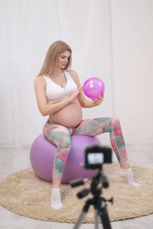 A sporty pregnant young woman blogger in sportswear talks about ball exercises. Stock fotó