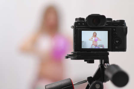 Pregnant female blogger shows fitness with ball. Camera screen view. Stockfoto