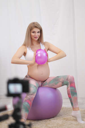 A sporty pregnant young woman blogger in sportswear talks about ball exercises. Stock fotó - 152492893