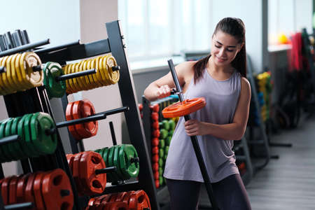 Beautiful sporty young brunette woman in sportswear in the gym. Prepares a barbell with weight for powerlifting.