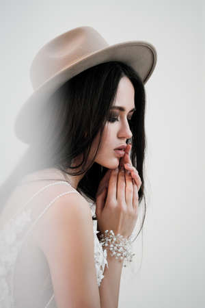 Portrait of the bride. A young attractive brunette woman with long black hair in braids. White wedding dress and beige hat. Rustic style, a bouquet of wheat spikes.