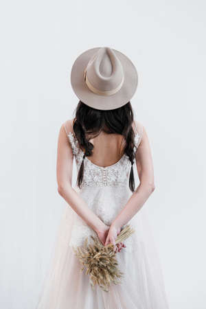 Portrait of the bride. A young attractive brunette woman with long black hair in braids. White wedding dress and beige hat. Rustic style, a bouquet of wheat spikes. Back view.