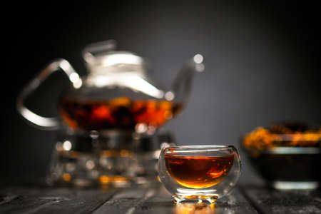 Horizontal photo of the tea set on a black background. Glass transparent teapot and cup. Black leaf tea is brewed.