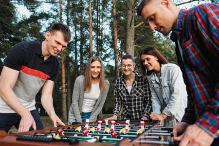Friends play table football or kicker outdoors. A party in nature. Players and fans rejoice in the victory.