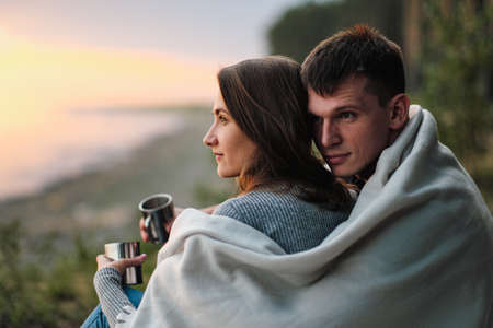 A couple in love sits on the riverbank at sunset. They cuddle, roll into a plaid and drink tea from a metal hiking mug. Travel and lifestyle.