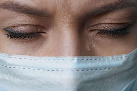 A female doctor therapist in a white robe, mask and gloves. Face close-up. The doctor cries and prays. Tears in eyes. Regret, anxiety and despair. Pandemic and virus epidemic. Coronavirus covid-19. Zdjęcie Seryjne