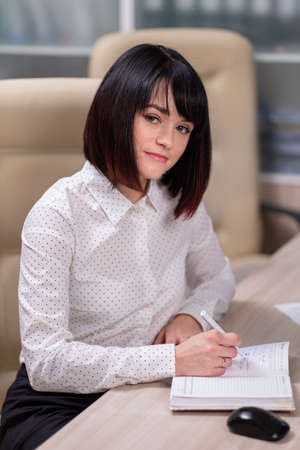 Portrait of a young beautiful woman, an office employee in a white shirt. A woman works at a computer, uses a tablet. Stock fotó - 152494378