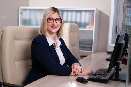 A young blonde woman with glasses is an office worker. Woman sits at the table and works at the computer. Businesswoman.