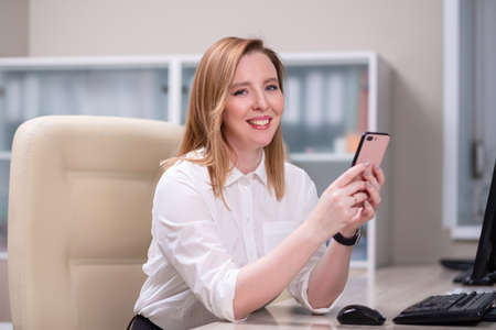 Portrait of a young beautiful woman, an office employee in a white shirt. A woman works at a computer, uses a tablet. Stock fotó - 152494392