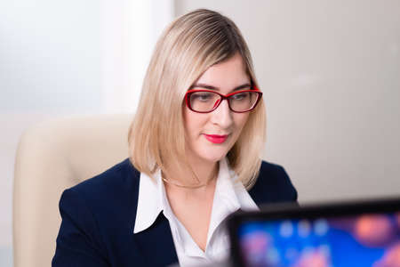 A young blonde woman with glasses is an office worker. Woman sits at the table and works at the computer. Businesswoman. Stock fotó - 152494394