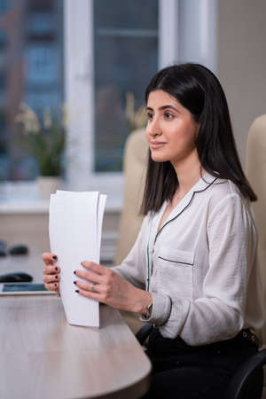Portrait of a young beautiful woman, an office employee in a white shirt. A woman works at a computer, uses a tablet.