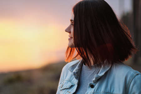 Attractive young red-haired woman with a short haircut at sunset in the woods. Rest in nature. Banque d'images