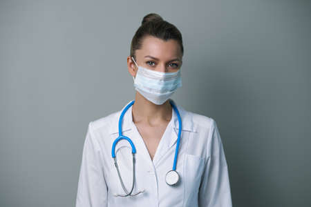 A female doctor in a white robe and mask with a stethoscope poses against a gray background.