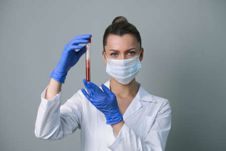 Blood test. A female medical worker holds a test tube with paciets blood. Coronavirus test.