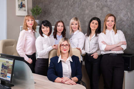 The womens team of seven professionals works in the office. Light office. Lawyers and accountants at work. Teamwork.