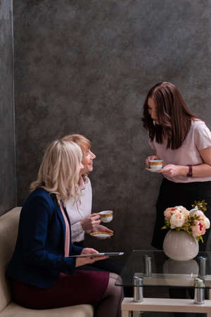Three young women socialize and drink tea at work. Grey wall and copy space.