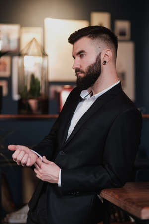 A young handsome man with a beard in a business suit in the interior of a restaurant in the loft style.