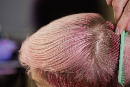 Hairdresser colorist dyes the hair of a woman to a client in different colors. The concept of a hair salon. 스톡 콘텐츠