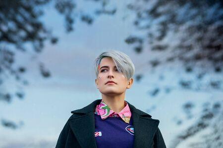 Portrait of a young beautiful woman in green coat with a short haircut and dyed hair. Grey main color and yellow, green, blue and red hair color. Posing in the street. Imagens
