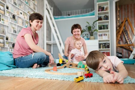 A young gay lesbian family with two children, a son and a daughter, spend time at home. They sit on the floor and play with childrens toys. The boys face is close-up.