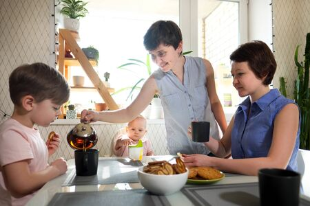 A young homosexual lesbian family with two children, a boy and a girl, at home in the kitchen forgiving the windows drinking tea and socialize. Family idilia and adoption.