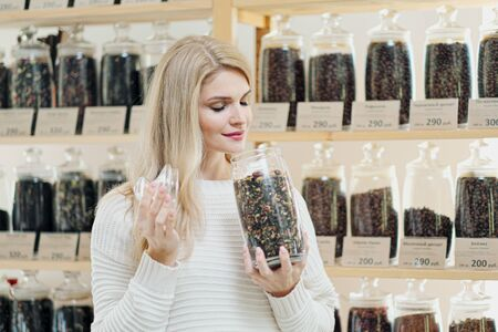 A young blonde woman chooses cereal coffee in the store. Test different sorts of coffee.