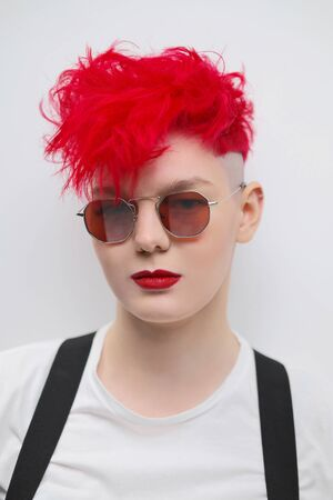 Portrait of a cool fashionable modern young girl. A short haircut with shaved temple. Dyed bright red hair. Red lipstick. Studio photo on a white background. Suspenders on checkered pants and sunglasses.