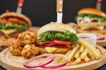 Combo set of fast food. Juicy delicious hamburger, French fries, chicken legs and sauce. Served wooden board and cutlery on a black background. Fast food restaurant. Food delivery.