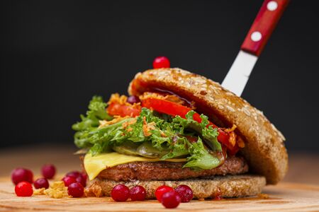 Delicious juicy burger with beef patty, bun, cranberry sauce and vegetables on a serving wooden board with a knife stuck on a black background. Food delivery. Fast food restaurant. Stock Photo