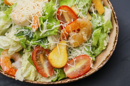 Caesar salad with shrimp, cheese and cherry tomatoes in a bowl on a black background. Imagens