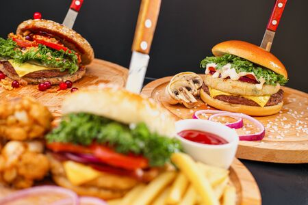 Combo set of fast food. Juicy delicious hamburger, French fries, chicken legs and sauce. Served wooden board and cutlery on a black background. Fast food restaurant. Food delivery. Imagens