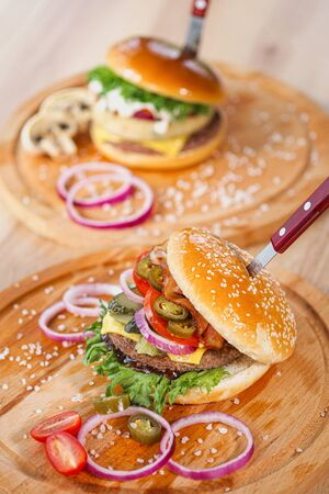 Delicious juicy burgers. Beef patty with toasted bun, salad and onions. Serving on wooden boards on the restaurant table. Fast food restaurant menu. Food delivery. Imagens