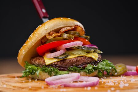 Delicious juicy burger with beef patty, bun and vegetables on a serving wooden board with a knife stuck on a black background. Food delivery. Fast food restaurant.