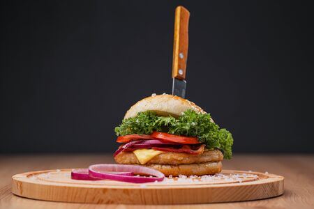 Delicious juicy hamburger on a served wooden board with a stuck knife, on a black background. Beef patties, vegetable buns and chopped onion rings. Imagens