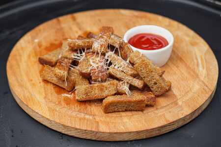 Rye fried in oil croutons of rye bread with red sauce. Snouts to beer on a wooden board.