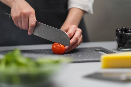 A female chef in a white uniform and a black apron in the restaurant kitchen. Preparing food. The cook cuts the vegetables with a large kitchen knife.