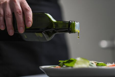A female chef in a white uniform and a black apron in the restaurant kitchen. Cooking. The cook pours olive oil from a green bottle. Grey background. Imagens