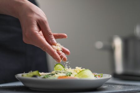 A female chef in a white uniform and a black apron in the restaurant kitchen. Cooking. The cook sprinkles grated cheese prepared food. Caesar salad.